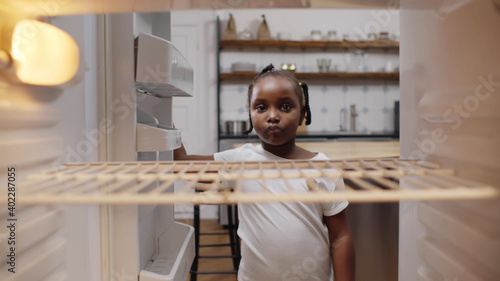 Photo Hungry poor little african girl look for food in empty fridge at home