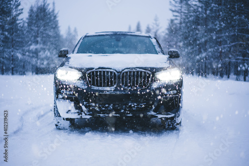 Canvas Print Modern black SUV on forest road on snowy winter day