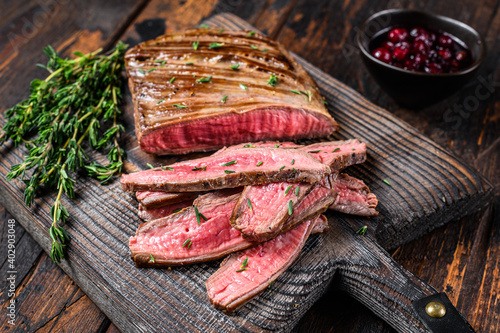 Foto Barbecue sliced flank beef meat steak on a wooden cutting board