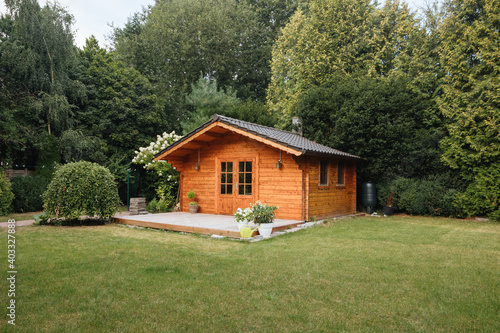 Fotografía Orange wooden hut in the garden with many tall trees