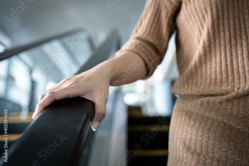 Wallpaper Mural Hand of young woman touching the escalator during Coronavirus pandemic,risk of c