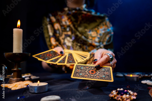 Canvas Print The fortune teller holds a fan of cards in her hands and holds out a card with one hand