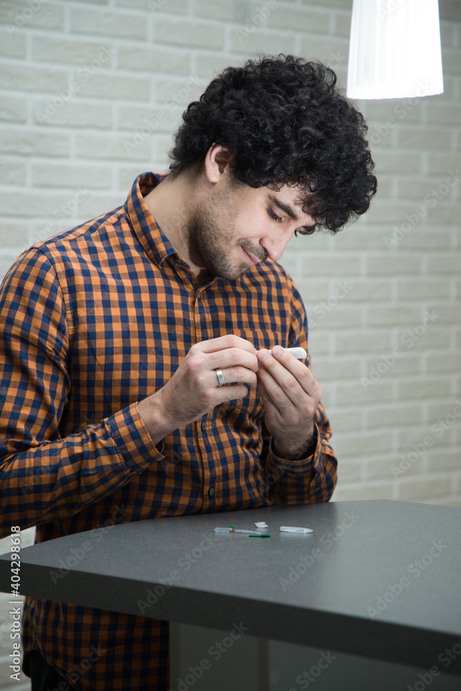 Obraz A handsome, solid curly-haired man in a plaid shirt makes a rapid test for antibodies to coronavirus covid 19 at home. He opened a rapid test kit, pricked his finger, and tested for Ig G and Ig M. fototapeta, plakat