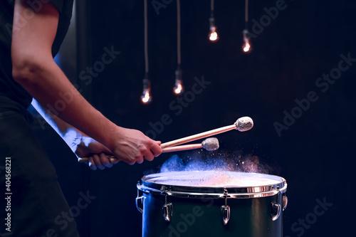Carta da parati The drummer plays with mallets on floor tom in dark room.