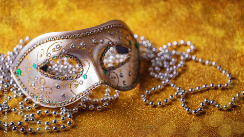 Photo Festive, colorful Mardi Gras or carnivale mask and beads on golden background