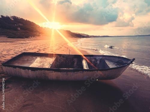 Fotografia Boat Moored On Shore Against Sky During Sunset