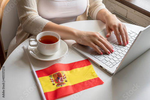 Wallpaper Mural Lonely woman freelancer with flag of Spain enjoying having breakfast with cup of coffee working on laptop sitting near window in cafe at morning