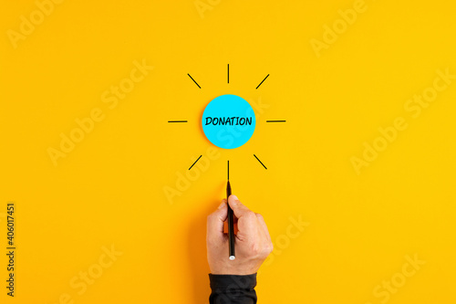 The word donation written on a blue circle badge with male hand drawing rays around