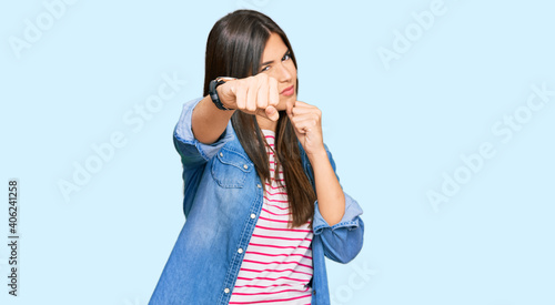 Fotografia, Obraz Young brunette woman wearing casual clothes punching fist to fight, aggressive a