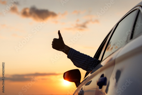Fotografiet Man On Car Against Orange Sky During Sunset