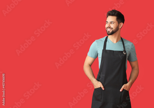 Young man wearing apron on color background Fotobehang