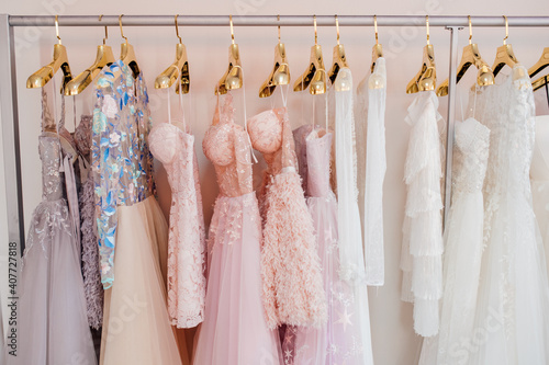 Canvastavla Collection of  beautiful evening dresses hanging on rack in dressing room