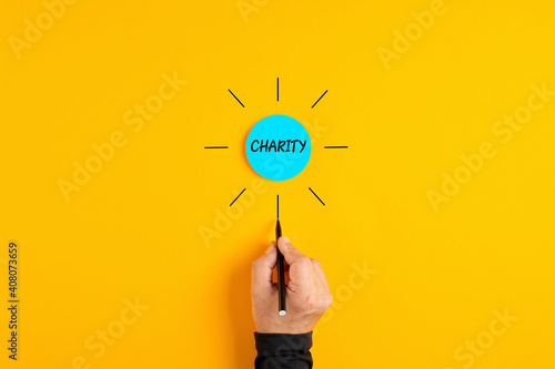 The word charity written on a blue circle badge with male hand drawing rays around the badge