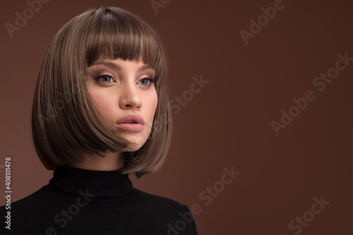 Portrait of a beautiful brown-haired woman with a short haircut on a brown backg Fotobehang