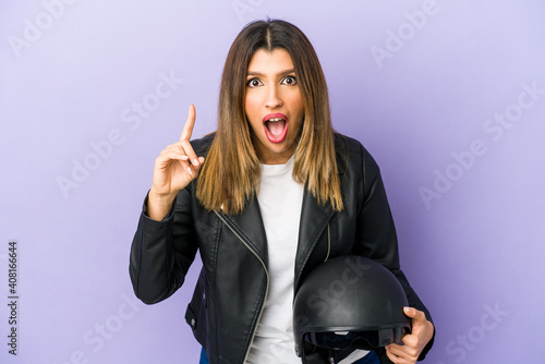 Obraz na plátne Young indian motorbiker woman isolated having an idea, inspiration concept