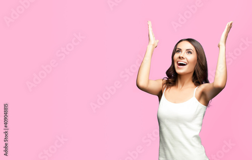 Murais de parede Portrait studio image of happy gesturing or praying young beautiful woman looking up, in white casual clothing, isolated over rose pink color background