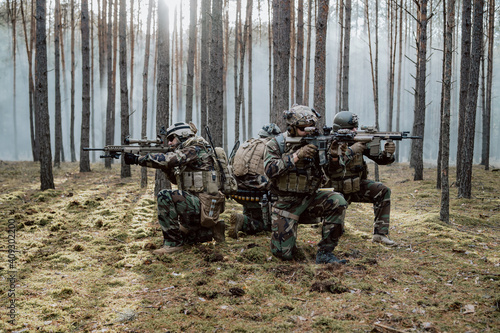 Canvas Print Squad of Four Fully Equipped Soldiers in Camouflage on a Reconnaissance Military Mission, Aiming Rifles
