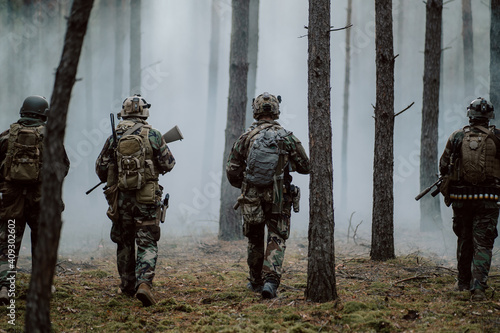 Obraz na plátne Squad of Four Fully Equipped Soldiers in Camouflage on a Reconnaissance Military Mission, Rifles Ready to Shoot