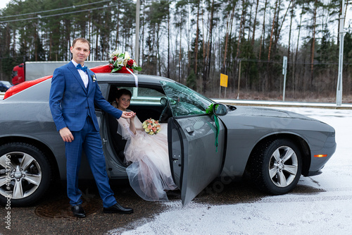 Foto the groom gives his hand to the bride from the car, the politeness and gallantry
