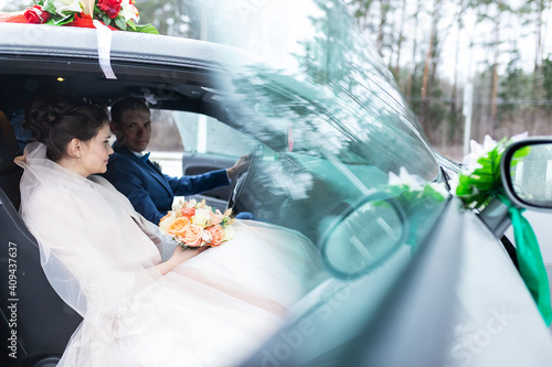 the groom gives his hand to the bride from the car, the politeness and gallantry Fototapete