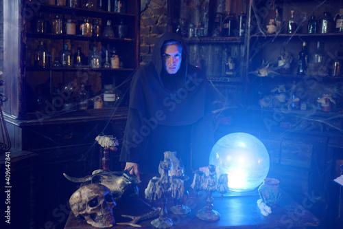 Photo Male exorcist in hood near the magic crystal ball