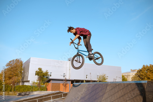 Fotografía Male bmx biker jumps on ramp in skatepark