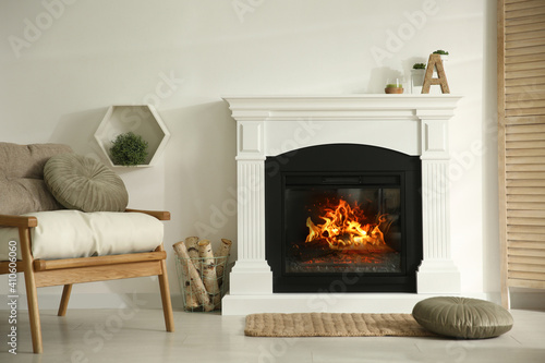Photo Bright living room interior with fireplace and basket of firewood