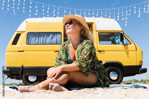 Foto Young blonde woman travelling by vintage campervan at the seaside