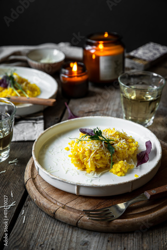 Fototapeta Rustic dinner with risotto all Milanese< wine and candles