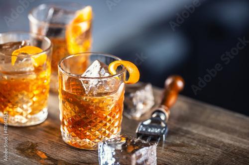 Fotografia Old fashioned rum drink on ice with orange zest garnish