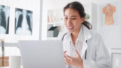 Slika na platnu Asian female doctor using laptop computer online video call remote talking to patient, prescribe medicine