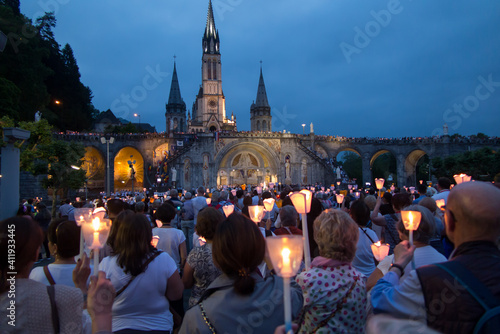 Fototapeta Lourdes, France, 24 June 2019: Evening procession with candles at the shrine of
