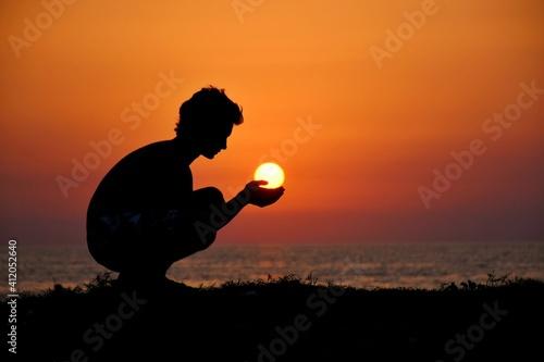 Fototapeta premium Optical Illusion Of Silhouette Man Holding Sun Over Sea During Sunset