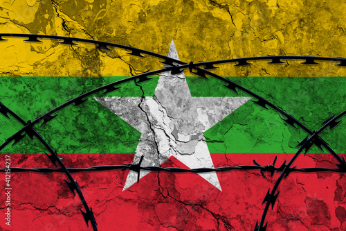 Fotografía The national flag of Myanmar (Burma) painted on a grungy wall with Barbed wire in the foreground