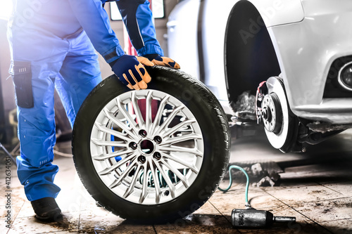 Auto mechanic working in garage and changing wheel alloy tire. Fototapet