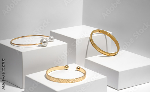 Fotografija Three modern golden bracelets on white geometric boxes