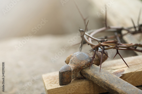 Tableau sur Toile Crown of thorns, wooden plank and hammer on grey background, closeup