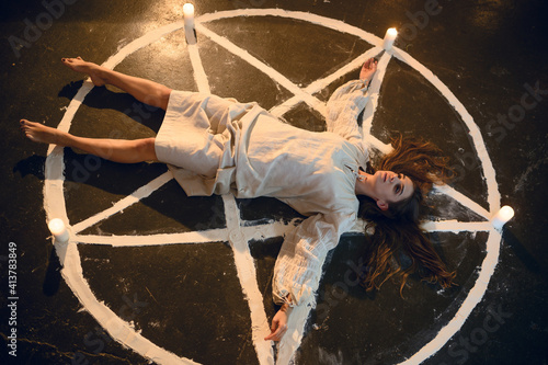 Photo Demonic woman lying in magic circle with candles
