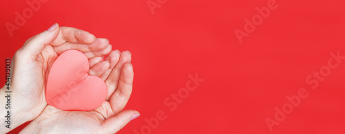 Canvas Print female hands hold a red heart on the palms isolated on a red background