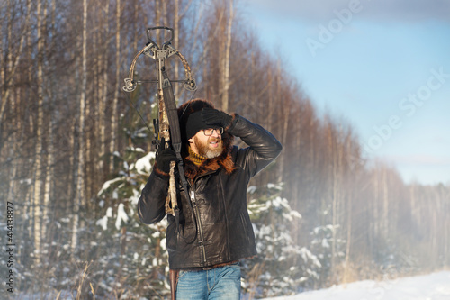 Obraz na płótnie a man of European appearance in the winter forest shoots from a sports crossbow