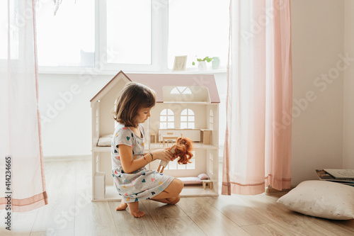 Canvas Print Girl playing with doll house