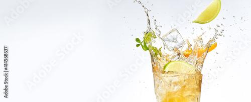 Tablou Canvas fresh fruits falling into cocktail glass, splashing on white background