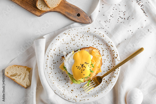 Photo Tasty sandwich with florentine egg, cheese and avocado on light background