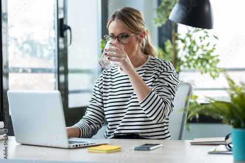 Beautiful mature business woman working with a laptop while drinking glass of water on a desk in the office at home Poster Mural XXL