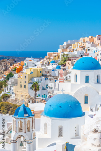 Churches and blue cupolas of Oia town at Santorini, Greece Poster Mural XXL
