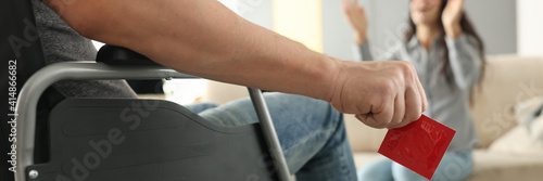 Canvas Man sits in wheelchair and holds condom in his hands opposite woman sits and happily raises his hands up