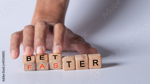 Fotografie, Obraz hand holding dice with text for illustration of better and faster words
