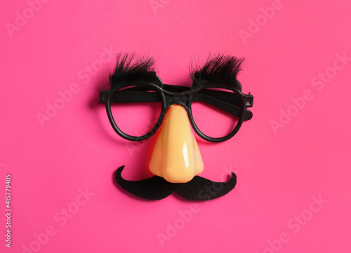 Платно Funny glasses on pink background, top view