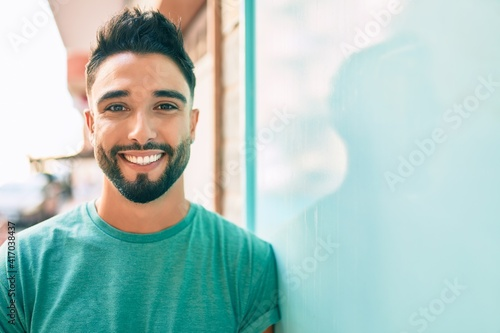 Fotografia Young arab man smiling happy leaning on the wall at the city.