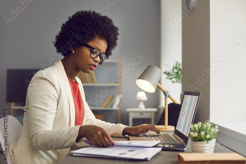 Foto Head shot focused millennial afro-american businesswoman financial advisor working with financial documents and laptop checking economic paper report